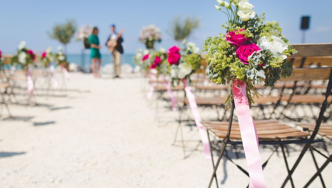 A beach wedding with a bouquet of flowers attached to a chair